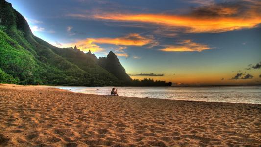 在海滩上看日落的女孩壁纸
