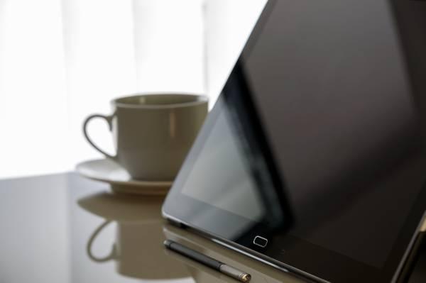 关闭黑色三星Galaxy Tab附近的白色陶瓷杯子和碟子高清壁纸